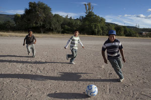 Three boys kicking a football around