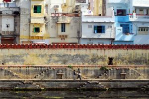 A man and his son on a shelf path at the edge of Lake Pichola