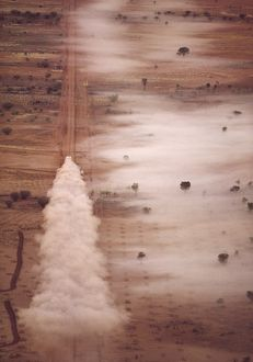 Vehicle driving along remote unsealed road with cloud of dust behind,