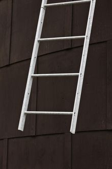White metal ladder against exterior wall