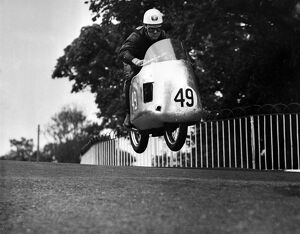 Bob McIntyre 's Norton takes off as he comes over Ballaugh Bridge during the