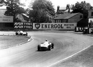 British racing driver Stirling Moss No 12, takes the lead from Fangio of Argentina