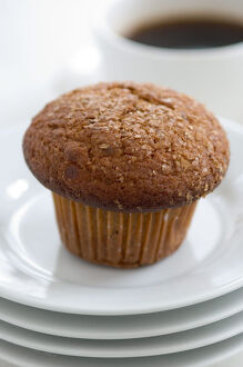 Cinnamon bran muffin on stack of white plates with cup of black coffee credit