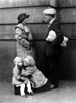A couple chatting while their children are kissing under the mistletoe 25 December 1921