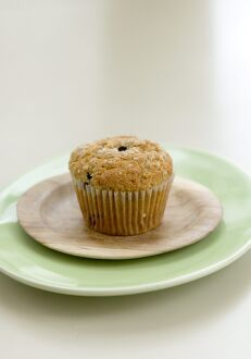 Healthy bran and raisin muffin on small wooden plate on green platter credit: Marie-Louise