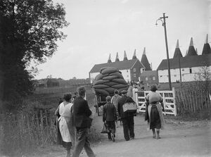 Hop pickers walking back to the oast houses with a loaded cart. <br> 1935