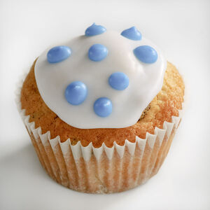 Iced cupcake with blue spots on white icing credit: Marie-Louise Avery / thePictureKitchen