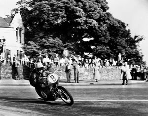Isle of Man: N Taniguchi of Japan takes the corner at speed, riding a 125cc Japanese honda