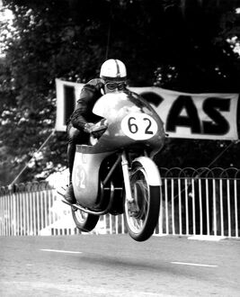 John Surtees ' MV machine is clear of the ground as he roars over Ballaugh Bridge