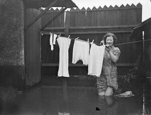Knee deep in flood water a housewife hangs out her washing at Maidenhead. 1 January