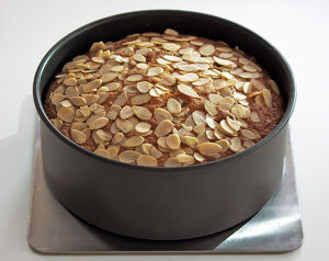 Light fruit cake topped with almonds in tin credit: Marie-Louise Avery / thePictureKitchen
