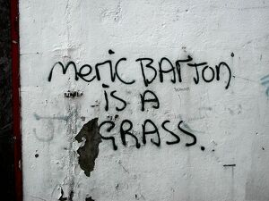 Meric Barton is a grass: graffiti on the side of a building denouncing a local person