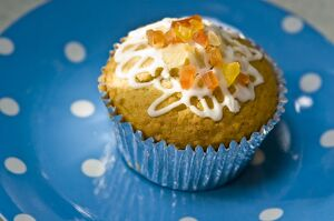 Muffin decorated with squiggly icing and candied peel on spotted blue plate credit