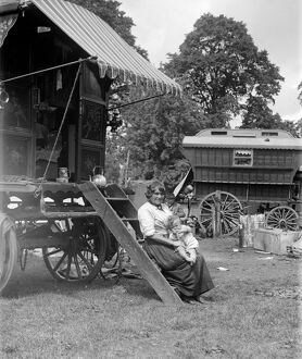 A Romany mother with her baby sitting on the steps of her caravan on Epsom Downs