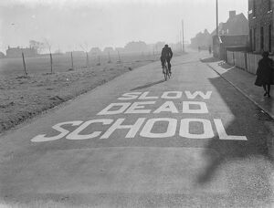A school sign painted on the road warning road users they are approaching a school area
