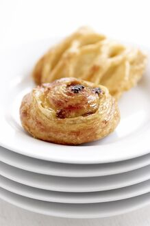 Small danish pastries on stack of white plates credit