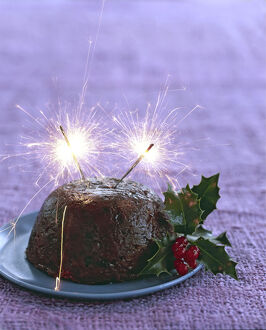 Traditional British Christmas pudding with with holly and berries and sparklers alight