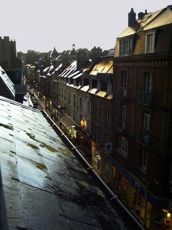 Typical French town houses with wet rooftops glistening in a golden light after rain