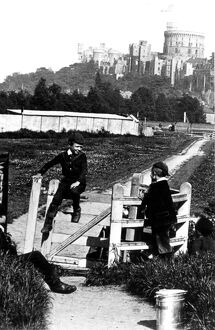 Four young boys playing games by the kissing gate with Windsor Castle in the background