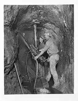 Two miners drilling with dust laying spray. King Edward Mine, South Condurrow, Camborne, Cornwall