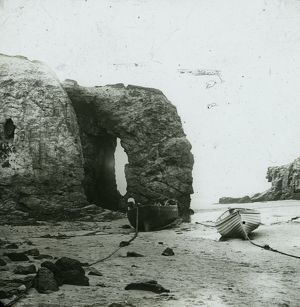 Perranporth Arch Rock, with boats on the beach. Cornwall