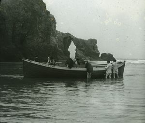 Thought to be Perranporth Arch Rock, with children playing on the boat 'The Ocean Waif&quot