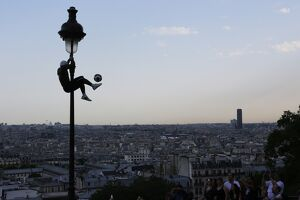 Iya Traore, a former professional football player, holds on to a lamppost as he performs