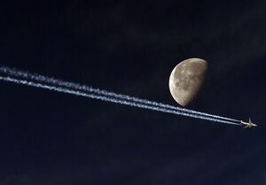 JETLINER VAPOUR TRAIL PASSING THE MOON