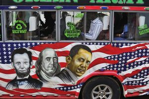 People sit in a 'matatu' minibus with a painting depicting US Presidents