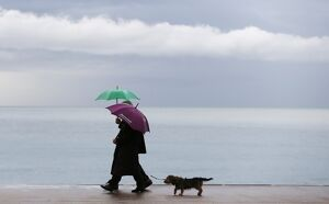 People walk on the 'Promenade des Anglais' during a rainy afternoon,