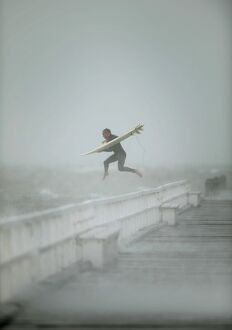 SURFER JUMPING OFF PORT PHILLIP BAY PIER AUSTRALIA