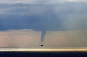 A waterspout forms on the horizon above the Mediterranean sea, off the coastal city