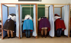 Women dressed in traditional Hungarian outfit prepare their votes in a polling station