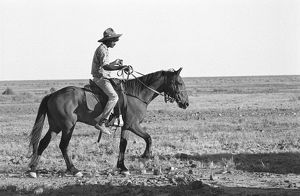 B&W image of a male jackeroo riding a horse in the desert.