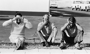 Three men sit on a roadside posing as the three wise monkeys.