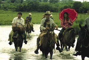 A small group of people on horseback ride across a shallow river
