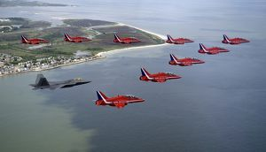 A F-22 Raptor flies in formation with the Royal Air Force Aerobatic Team, The Red Arrows