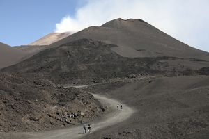 Hikers walking towards summit area of Mount Etna volcano, Sicily, Italy
