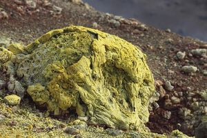 Lava bomb coated in yellow sulphurous fumarole deposits