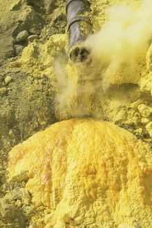 Liquid sulphur running out of a pipe in Kawah Ijen Volcano Sulphur Mine, Java, Indonesia