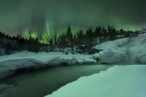 A wintery waterfall and aurora borealis over Tennevik River, Norway
