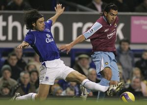 Everton's Valente challenges West Ham United's Tevez for the ball during