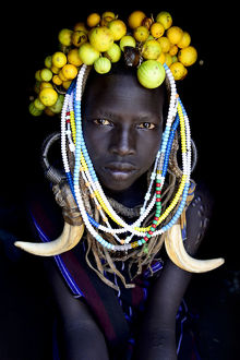 requests/young girl wearing traditional headdress mursi tribe
