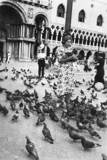 Woman surrounded by pigeons, St Mark's Square, Venice, Italy, 1938. Artist: Unknown