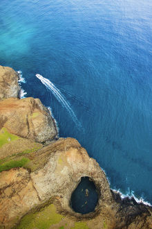 Aerial View Of The Rugged Coastline And A Boat In The Pacific Ocean Along An Hawaiian