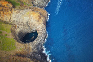 Aerial View Of The Rugged Coastline And Tide Pool In A Hole Along An Hawaiian Island