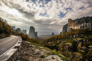 Landscape Of Rugged Cliffs, Road, Autumn Foliage And Monastery Rousanou In The Distance