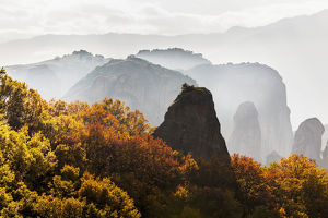 Low Cloud Around The Rugged Cliffs With Foliage In Autumn Colours; Meteora, Greece