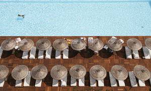 Man Swimming In Pool By Sunloungers, Aerial View